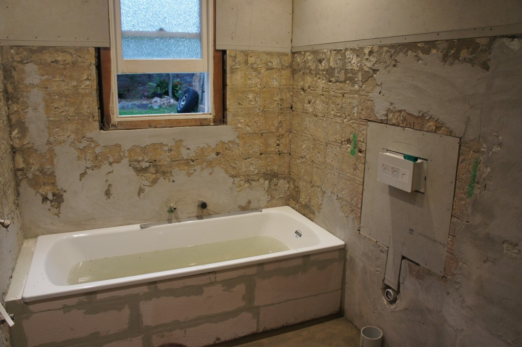New bath tub set into place. Rough-in complete by plumber, for bath, toilet, vanity and shower.